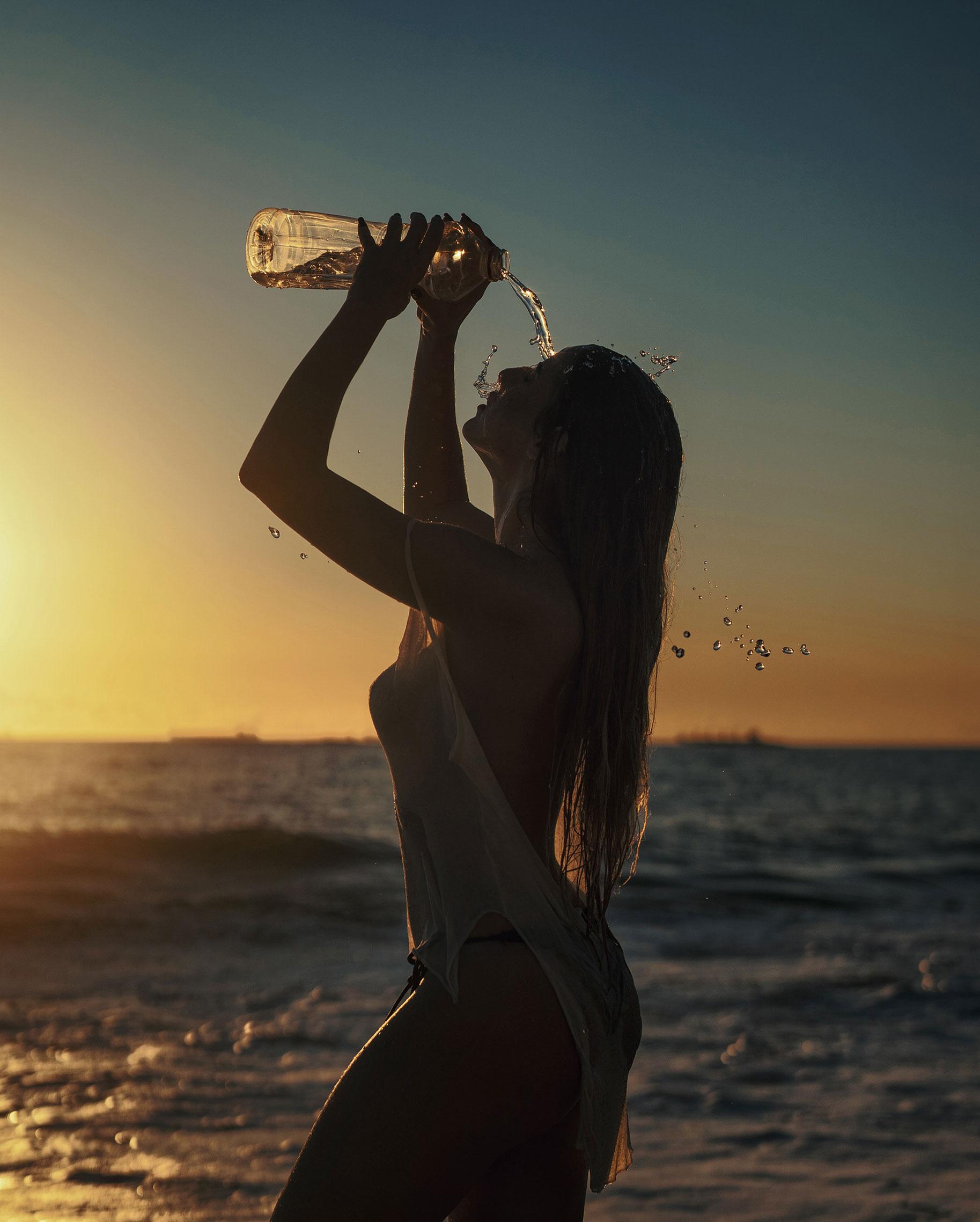 Девушка купается в море на закате / фото 03