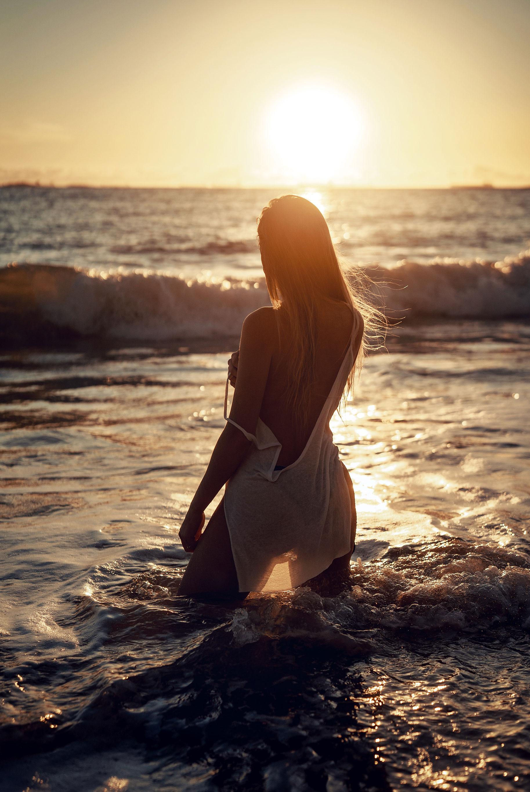 Девушка купается в море на закате / фото 04