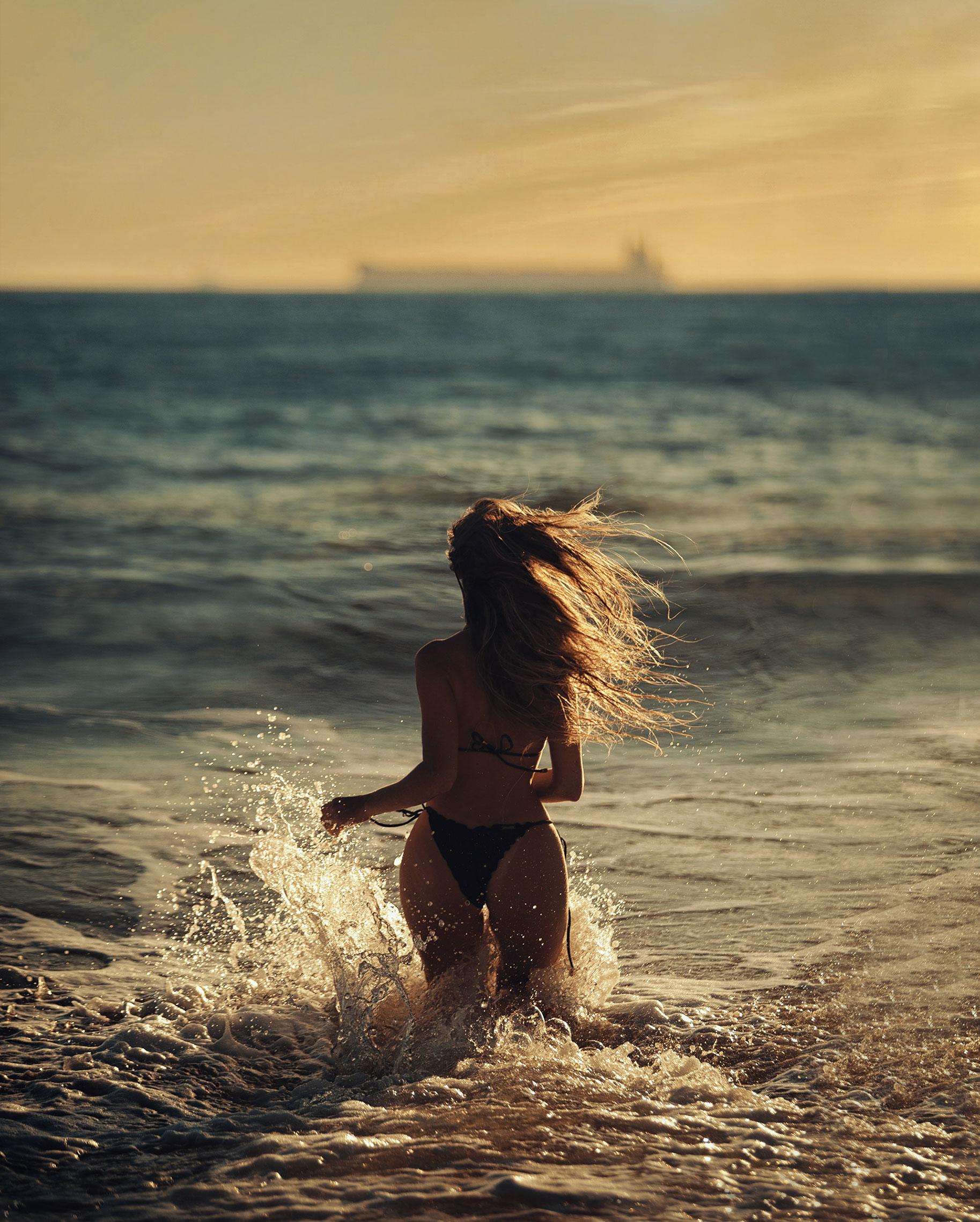 Девушка купается в море на закате / фото 06